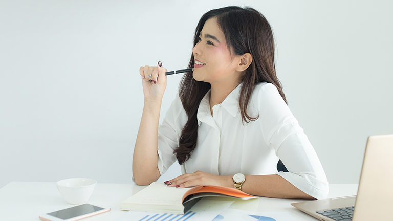 Young asian business woman smiling and thinking idea about work at her workplace.